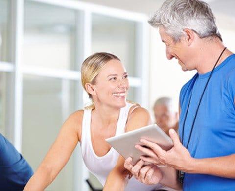 Trainer berät Frau im Fitnessstudio